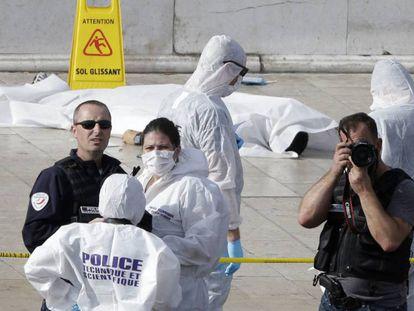 Miembros de la Policía científica investigan la zona del suceso. Al fondo, un cadáver cubierto en una sábana blanca.