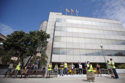 Una docena de trabajadores afectados por ERTE protesta frente a la delegación del SEPE en Barcelona.