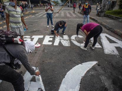 Jóvenes colombianos realizan pintadas de protesta en una avenida de la ciudad de Cali, el 8 de mayo.