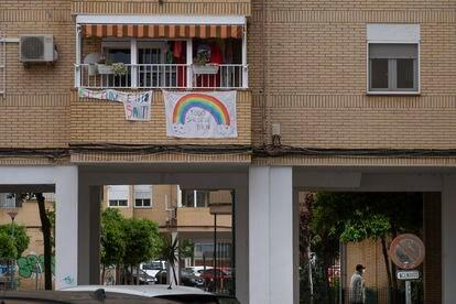 Una pancarta con el arcoiris con las palabras 'Todo saldrá bien' en un bloque de viviendas de Sevilla.