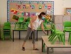 Una profesora prepara un aula para los alumnos que se reincorporan clase tras el confinamiento, el jueves en Haifa.