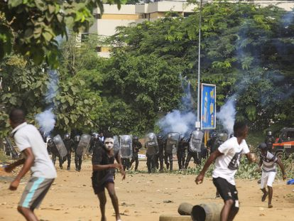 Jóvenes huyen de la Policía, que usa gases lacrimógenos para dispersarlos, durante las protestas contra un tercer mandato de Alassane Ouattara en Costa de Marfil, este jueves en Abiyán.