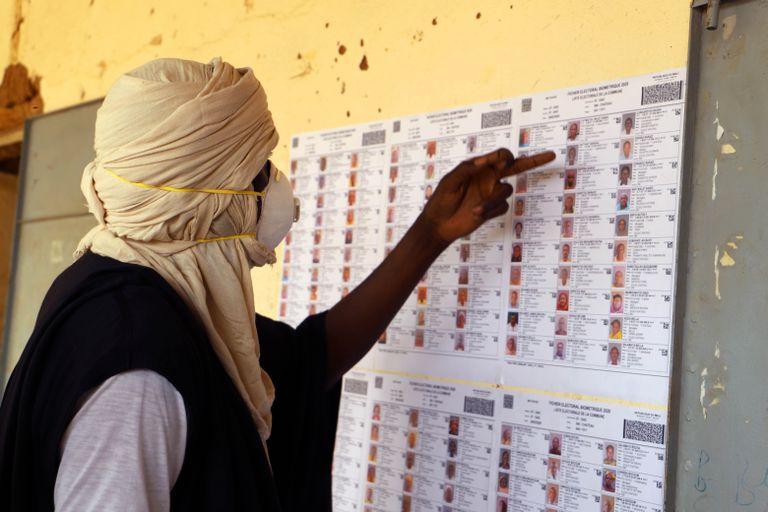Un votante con mascarilla busca su nombre en el censo de un colegio electoral de Gao, en Malí, durante las elecciones legislativas celebradas este domingo.