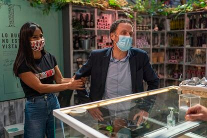 Begoña Villacís tries to take Edmundo Bal, Citizens' candidate for the presidency of the Community of Madrid, during his visit to the San Antón Market, in the Chueca neighborhood of Madrid.