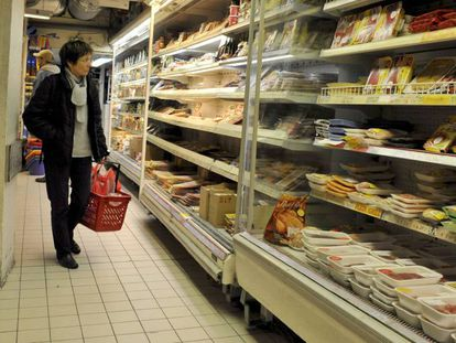 Un cliente observa las estanterías de un supermercado.