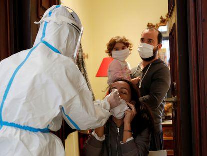 Un sanitario toma muestras para la prueba de la covid a una familia en su vivienda de Roma (Italia).
