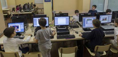 Niños con ordenadores en la clase de informática de un colegio público.