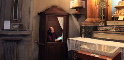 Un sacerdote usa su tableta en el confesionario, situado junto a una de las cuatro pantallas de televisión.