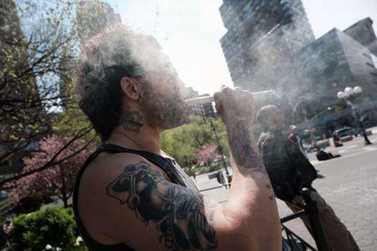 Un hombre fuma en Nueva York, el 20 de abril, junto a un puesto de Joints For Jabs.