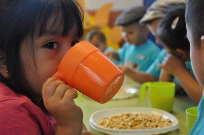 Un grupo de niños en un comedor escolar.