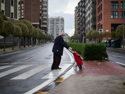 Un hombre regresa a su domicilio con la compra durante el Sábado Santo en Pamplona.