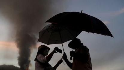 Una pareja se protege de las cenizas del volcán Cumbre Vieja en la mañana de este lunes.