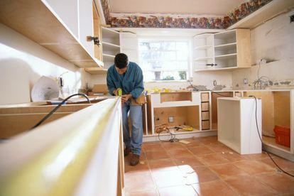 Un operario monta la cocina de una vivienda.