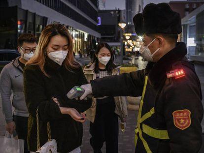 Clientes de un centro comercial en Beijing, China, sometiéndose a un control antes de acceder.