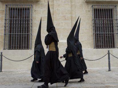 Nazarenos de la Hermandad de los Estudiantes abandonando este martes la Universidad de Sevilla tras la cancelación de su estación.