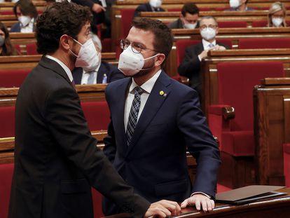 El líder de ERC, Pere Aragonès, conversa con el consejero de Territorio Damià Calvet, a la izquierda, en el Parlament catalán.