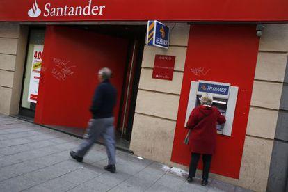 Una mujer utiliza un cajero del Banco Santander en Madrid.