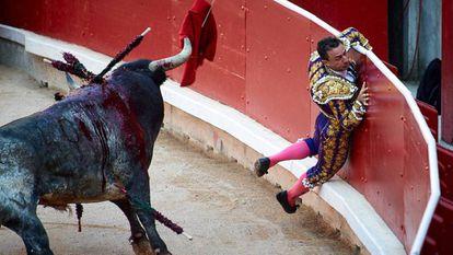 Momento en el que Rafaelillo es estampado contra la barrera por un toro de Miura en Pamplona.
