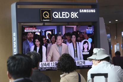Varias personas miran en una televisión imágenes de archivo del dueño de Samsung, Lee Kun-hee.