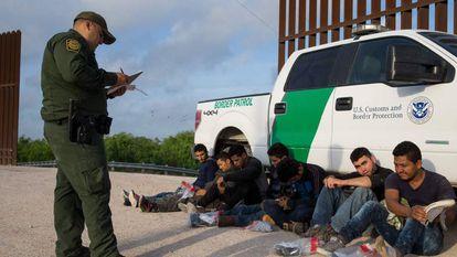 Un agente de la Patrulla Fronteriza detiene a un grupo de inmigrantes ilegales en la frontera entre México y Estados Unidos.