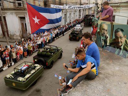 Cubanos presencian desde su azotea el paso de los restos del. expresidente Fidel Castro, en Santa Clara, Cuba, en diciembre de 2016.
