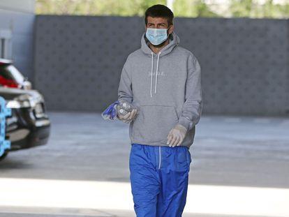 Pique accede a la ciudad deportiva del Barcelona con guantes y mascarilla.