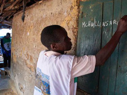 El enfermero comunitario Lansana Lavalie escribe en la fachada de una casa el número de mosquiteras que ha repartido en ella durante una campaña nacional de distribución en Gondama, Sierra Leona, en junio de 2017.