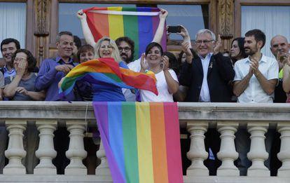 El colectivo LGTB despliega su bandera en el balcón del Ayuntamiento de Valencia.