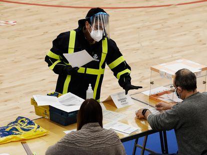 Un  cartero entrega el voto por correo en una mesa durante las elecciones catalanas del 14 de febrero.