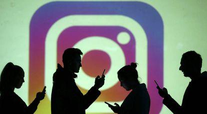 Usuarios de móviles, frente al logotipo de Instagram.