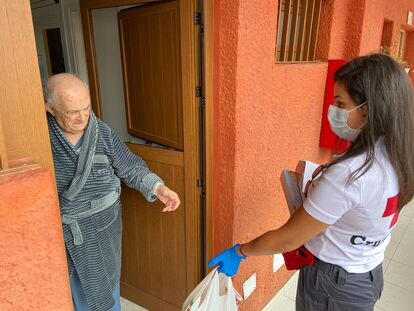 Una voluntaria de Cruz Roja presta ayuda a una persona mayor durante el estado de alarma.