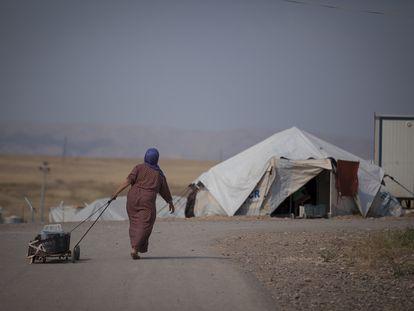 Una mujer siria transporta un cubo de agua en el campo de refugiados de Darashakran, en Erbil, Irak, en 2015.