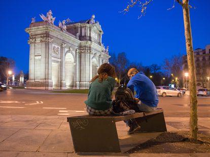 Dos jóvenes sentados en un banco cercano a la Puerta de Alcalá (Madrid) el pasado sábado.