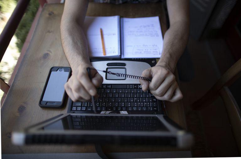 Un hombre teletrabaja desde su casa con un portátil, en Madrid.