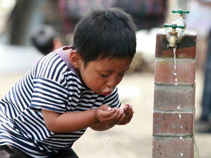 Niño bebe de una fuente de agua en Sololá, Guatemala.