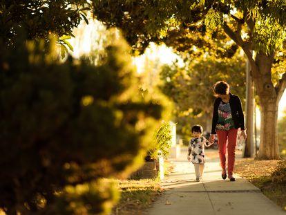 Una madre pasea con su hija por una avenida.