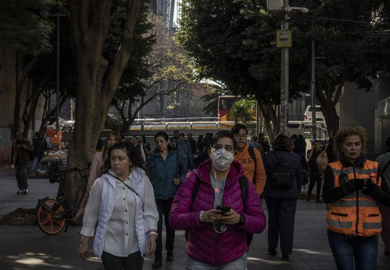 Una mujer camina con un cubre bocas en Ciudad de México este viernes.