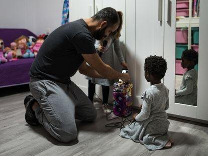 Paco, padre de acogida de Atu, de cuatro años, juega con ella y su otra hija, en su casa de El Hierro.