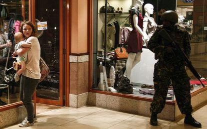 Un soldado apostado en el centro comercial ante una mujer y su hijo.