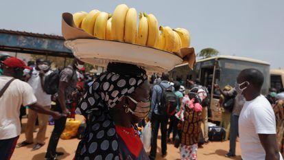Una vendedora callejera carga con una cesta de plátanos sobre su cabeza por una concurrida calle de Dakar, capital senegalesa, en mayo de 2020.