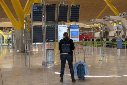 Aeropuertos y estaciones de tren, prácticamente vacíos. Una mujer que iba a viajar en uno de los pocos vuelos de Barajas durante el primer estado de alarma, en abril.