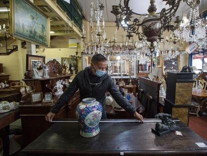 Fernando Nistal, director de la tienda Mersema, en Las Rozas (Madrid), mide una mesa de segunda mano.