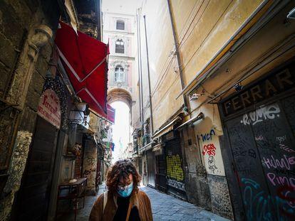 Una mujer con una mascarilla camina por el desértico centro de Nápoles este lunes.