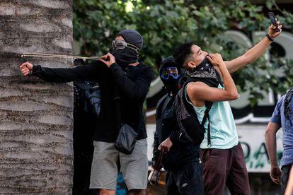 Un joven se hace un selfi mientras otro apunta un tirachinas durante una protesta en Santiago de Chile.