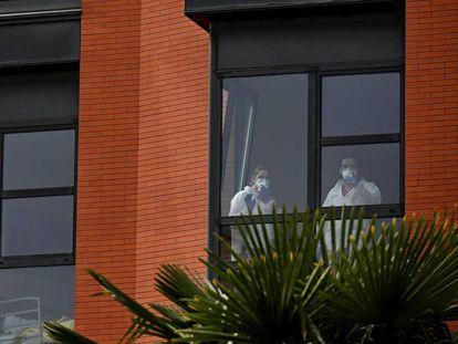 Dos trabajadoras miran por la ventana desde el interior de la residencia de ancianos Monte Hermoso, este miércoles, en Madrid.