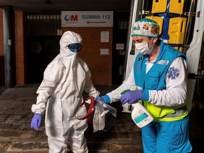 Miembros del equipo sanitario del Summa realizan el proceso de colocación y retiro de un EPI, durante su guardia de 24 horas en el centro de salud Las Águilas, en Madrid.