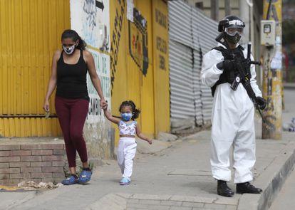 Un soldado con un traje para la covid vigila una calle de Ciudad Bolívar, uno de los barrios más afectados por la pandemia en Bogotá.