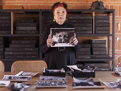 Graciela Iturbide sostiene una de sus fotografías de Avándaro en su estudio.