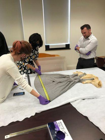 Los expertos del Museo de Historia Estadounidense del Instituto Smithsonian (de izquierda a derecha) Dawn Wallace, Sunae Park Evans y Ryan Lintelman examinan el vestido de Dorothy de 'El mago de Oz' encontrado en la Universidad Católica de América, en Washington.