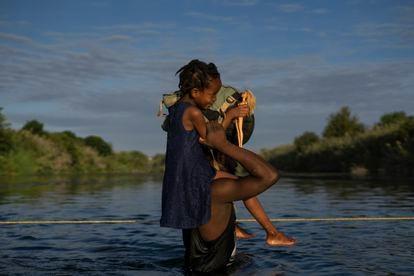Un hombre lleva a su hija a hombros para cruzar el Río Bravo entre Del Río y Ciudad Acuña.